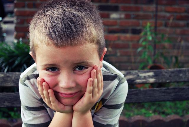 chlapec držící si tváře