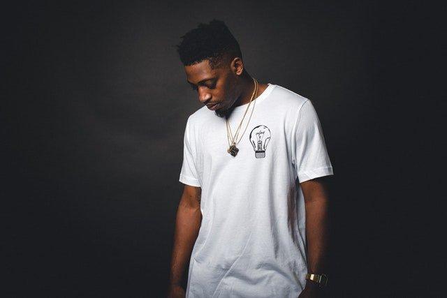 mladý muž v bílém tričku s potiskem