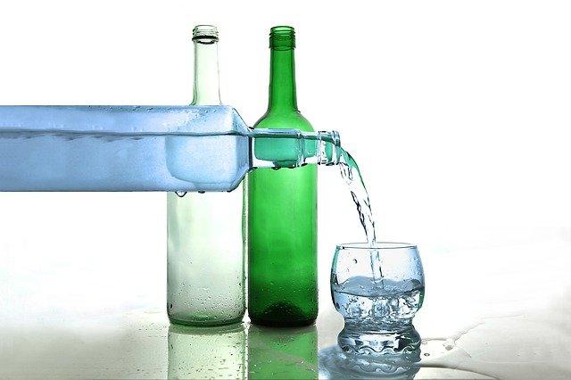 Dvě stojící lahve, ze třetí je nalévána do skleničky čirá tekutina