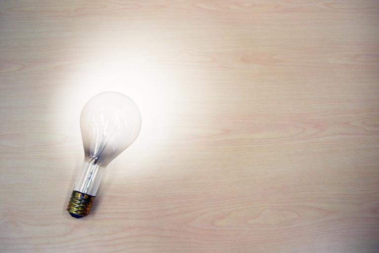 Žárovka na světlém podkladu dřeva, svítí