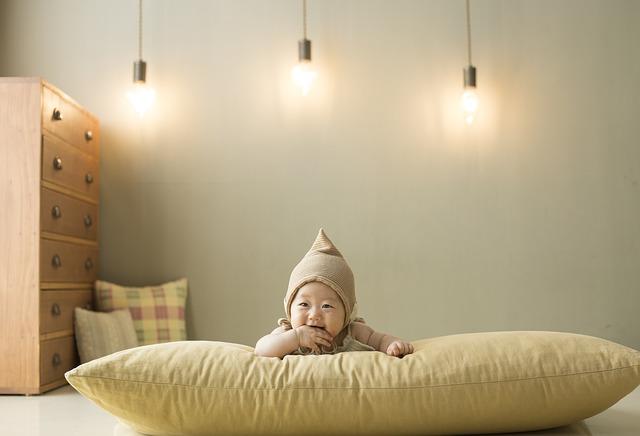 Malý Číňan v béžové čepici leží na velkém béžovém polštáři, za ním svítí tři žárovky